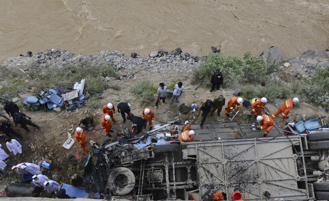 Rescuers worked around an overturned tour bus after it fell off a cliff in Tibet. Photo courtesy Associated Press