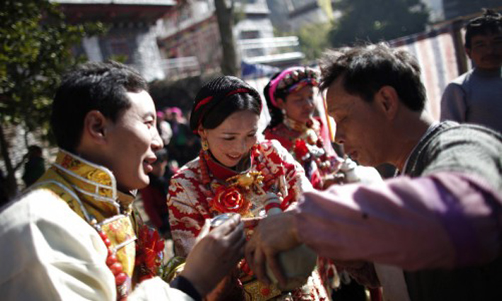 Erja, center, and Baima, left, celebrate with guests during their traditional Tibetan wedding near Danba, Sichuan Province Jan. 26, 2012. China has turned to promoting interracial marriage in an apparent attempt to assimilate Tibetans and stamp out rebellious impulses. (Photo courtesy: Carlos Barria / Reuters/REUTERS)