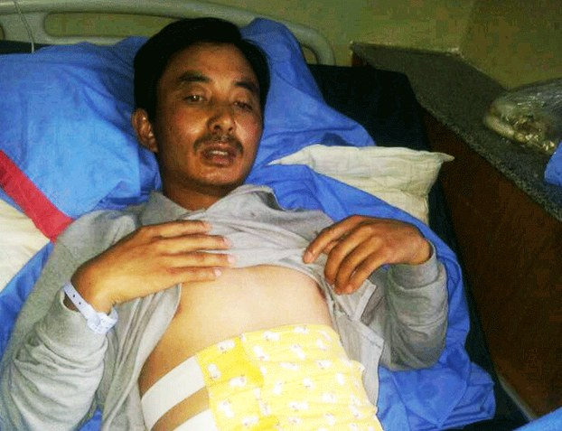 Tenzin Rinchen lies injured in bed in an undated photo. (photo courtesy RFA)