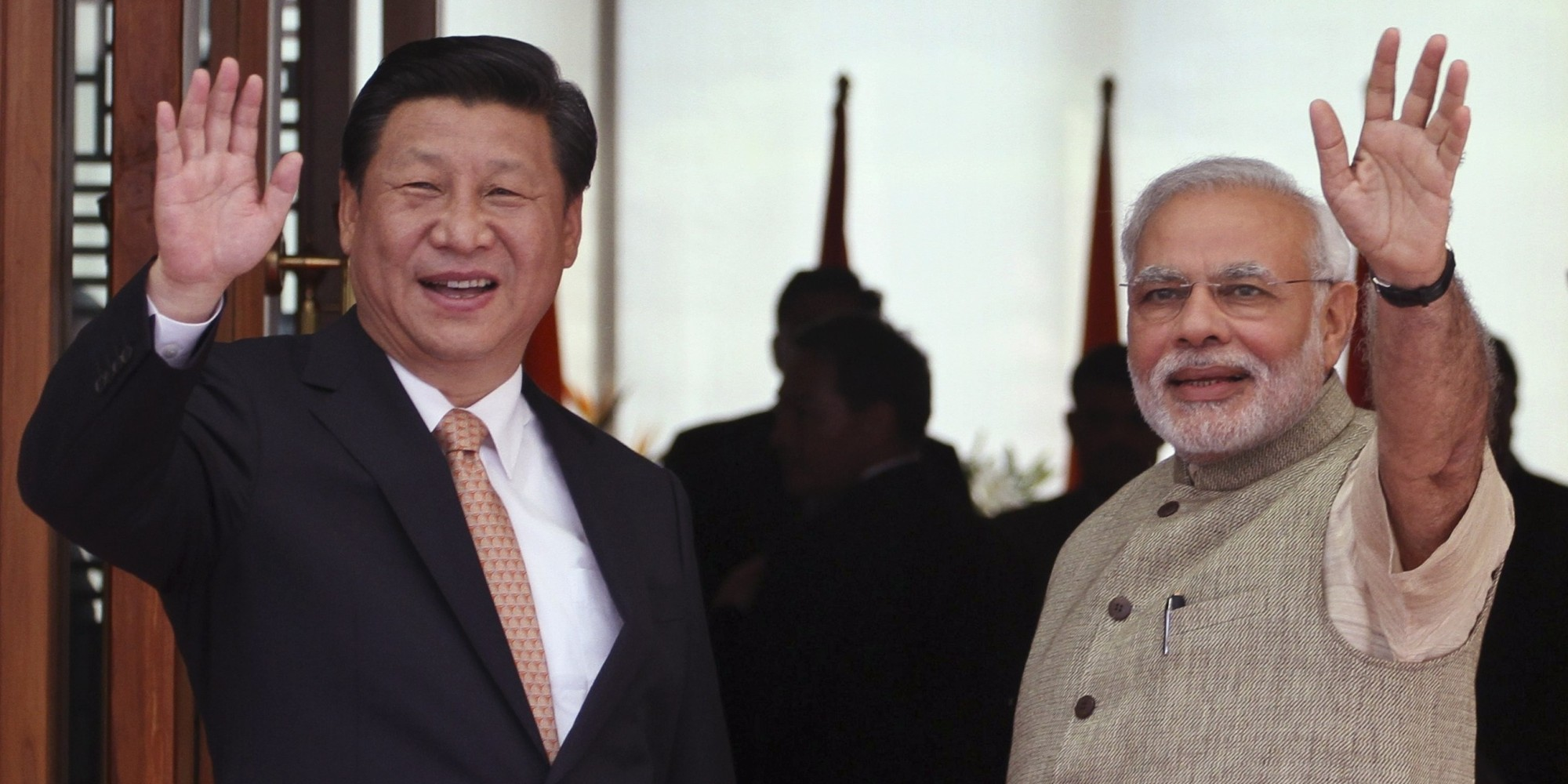Indian Prime Minister Narendra Modi, right, and Chinese President Xi Jinping wave to the media as Modi welcomes Xi upon his arrival at a hotel in Ahmadabad, India, Wednesday, Sept. 17, 2014.  Xi landed in Modi's home state of Gujarat on Wednesday for a three-day visit expected to focus on India's need to improve worn out infrastructure and reduce its trade deficit. (AP Photo/Ajit Solanki)
