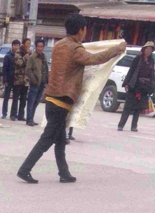 Pasang Wangchuk displays a protest banner in downtown Kardze, Oct. 3, 2014. (Photo courtesy: TCHRD)