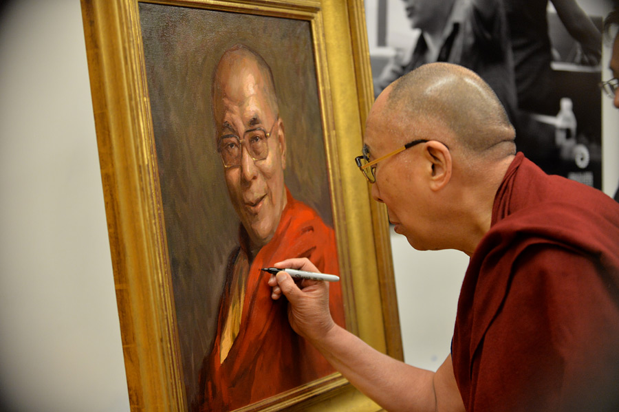 His Holiness the Dalai Lama signing a portrait of himself during his visit to Boston, MA, USA on October 31, 2014. (Photo courtesy/Sonam Zoksang, OHHDL)
