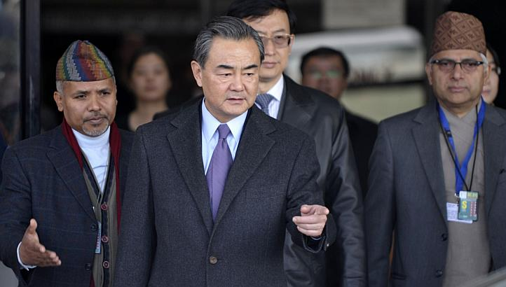 Chinese Foreign Minister Wang Yi (middle) gestures following his arrival at Tribhuvan International Airport in Kathmandu on Dec 25, 2014. (Photo courtesy: AFP)