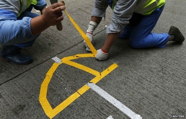 "Workers remove a logo left by pro-democracy protesters in the shape of an umbrella during a clearance at the last ""Occupy"" protest site blocking a main road at Causeway Bay shopping district in Hong Kong The mass protest has become known as the Umbrella movement. Hong Kong police have arrested several people as they cleared the last remaining pro-democracy protest site. (Photo courtesy/BBC/Reuters)"