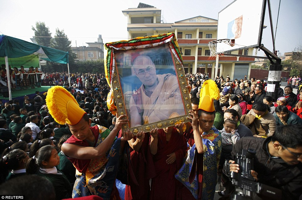 Young Tibetan monks carry a portrait of the Dalai Lama through the streets of Nepal. (Photo courtesy: DailyMail)