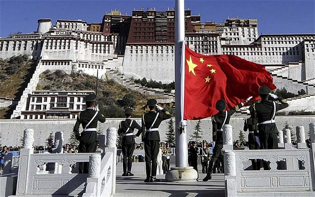 Chinese soldier hoisting Chinese flag in front of Potala Palace, Lhasa, Tibet. (Photo courtesy: AP)