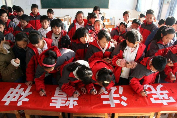 Students of a rural school sign their names on a banner which reads 'Promote the spirit of the constitution, build a harmonious campus' in Shandong province, Dec. 4, 2014. (Photo courtesy: RFA)