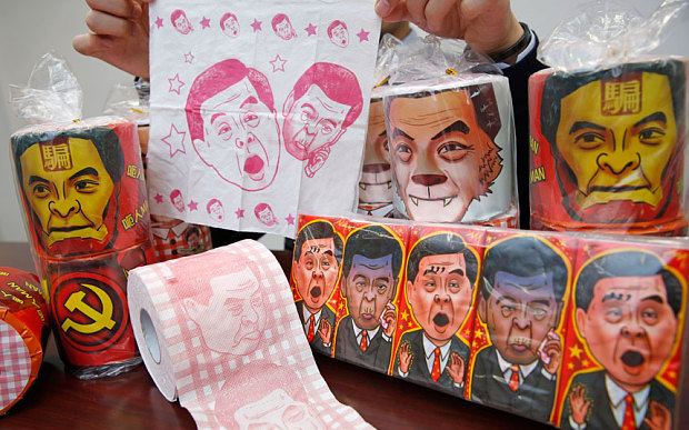 Rolls of toilet paper and packages of tissue paper printed with images of pro-Beijing Hong Kong Chief Executive Leung Chun-ying are shown by Hong Kong Democratic Party Vice Chairman Lo Kin-hei at his office in Hong Kong  (Photo courtesy: AP)