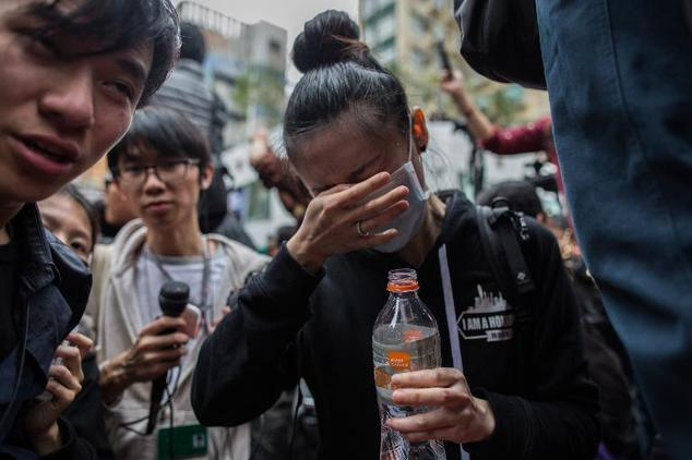 Protesters and members of the media react after being pepper sprayed by police during a protest in Hong Kong, on March 1, 2015/Anthony Wallace /AFP)