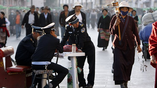 Guards keep watch over Buddhist pilgrims near the Jokhang temple in Lhasa. (Photo courtesy: Greg Baker/AP)