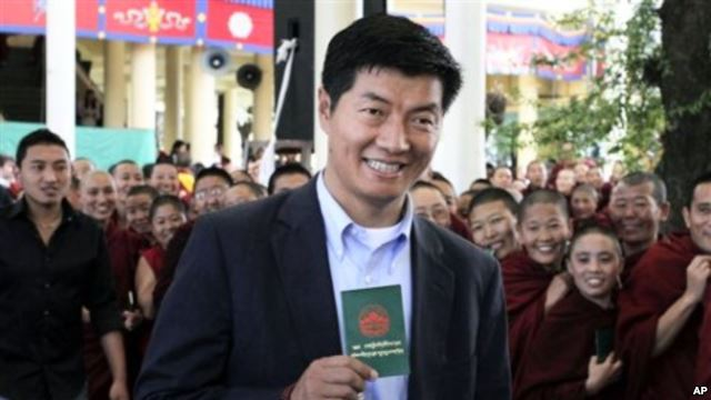 Sekyong Lobsang Sengey, shows his green book as he arrives to cast his vote in Dharmsala, India.