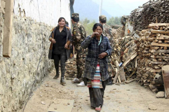 Residents cry as they walk past damaged houses to safer areas, after a 7.9 magnitude earthquake hit Nepal, in Kyiron. (Photo courtesy: REUTERS/Stringer)