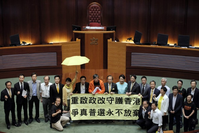 "Pro-democracy lawmakers display a yellow umbrella and a banner stating ""Reopen political reform to protect Hong Kong, never give up to fight for true universal suffrage"" after 28 lawmakers voted against the election reforms proposals at the Legislative Council in Hong Kong on June 18, 2015. (Photo courtesy: AP Photo/Vincent Yu)"
