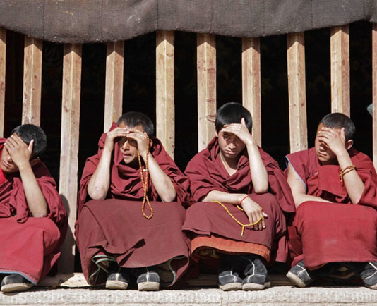 Tibetan monks shield their eyes from the sun as they watch others dancing at the Kirti Monastery near the town of Langmusi, Tibet. (Photo courtesy Reuters)