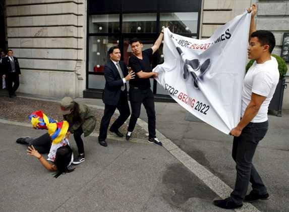 A hotel security staff (C) tries to take a banner from Tibetan protesters outside the Beijing 2022 Winter Olympic Candidate City presentation at the Palace hotel in Lausanne, Switzerland June 10, 2015. (Photo courtesy Reuters/Ruben Sprich)