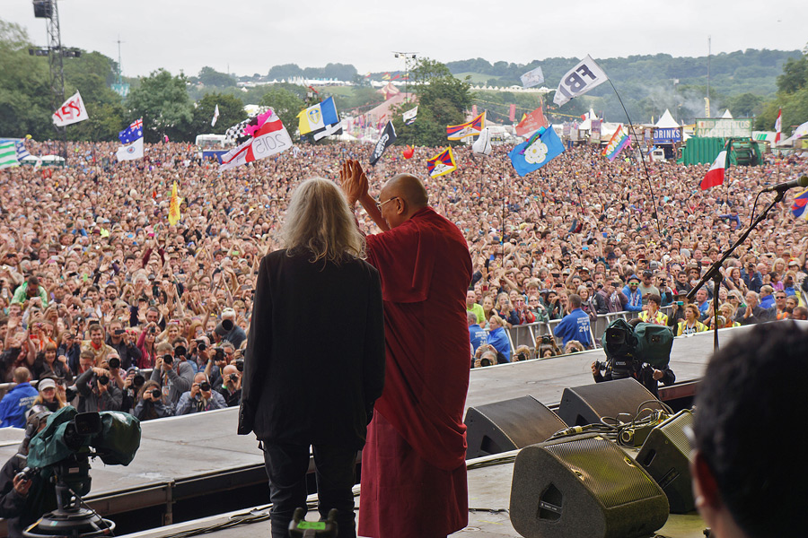 His Holiness the Dalai Lama, along with Patti Smith, waving to the crowd of over 120,000 at the Pyramid Stage at the Glastonbury Festival in Glastonbury, Somerset, UK on June 28, 2015. (Photo courtesy/Jeremy Russell/OHHDL)
