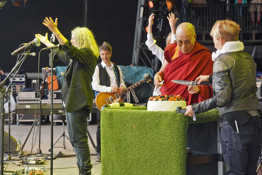 Patti Smith leading the crowd in singing Happy Birthday as His Holiness the Dalai Lama cuts a cake in honor of his 80th birthday at the Glastonbury Festival in Glastonbury, Somerset, UK on June 28, 2015. (Photo courtesy/Jeremy Russell/OHHDL)