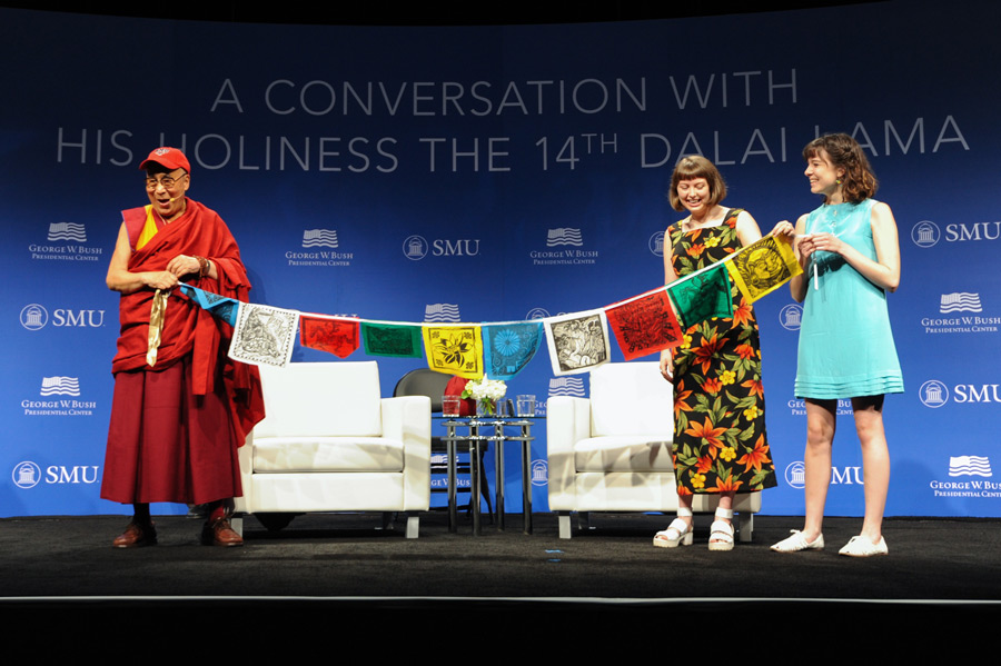 Members of the Tibet Club of Booker T Washington School presenting prayer flags they've made to His Holiness the Dalai Lama at the start of his talk at Southern Methodist University's Moody Center in Dallas, Texas, USA on July 1, 2015. (Photo courtesy/Bush Center)
