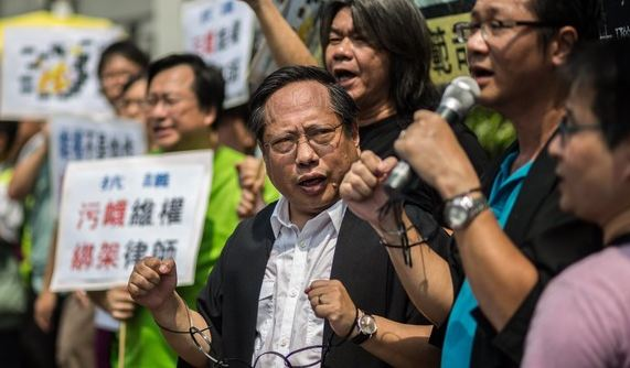 Protesters wear mock handcuffs at a rally in Hong Kong following the arrest of human rights lawyers in China. (Photo courtesy: ft.com)