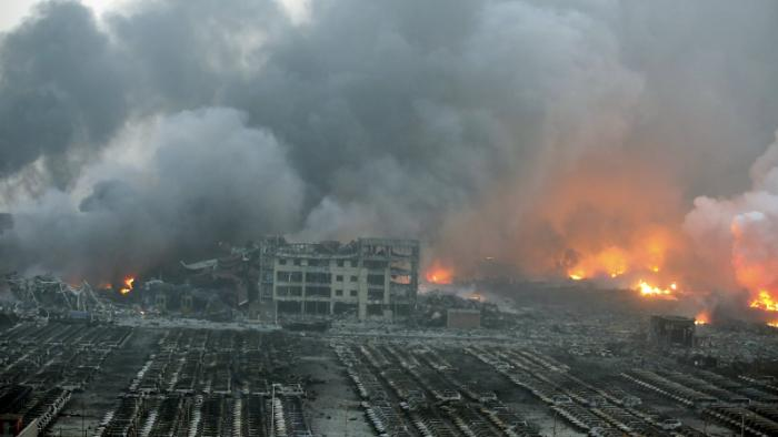 Fire and smoke rise at the site of the massive explosions in Tianjin, China, August 13, 2015.