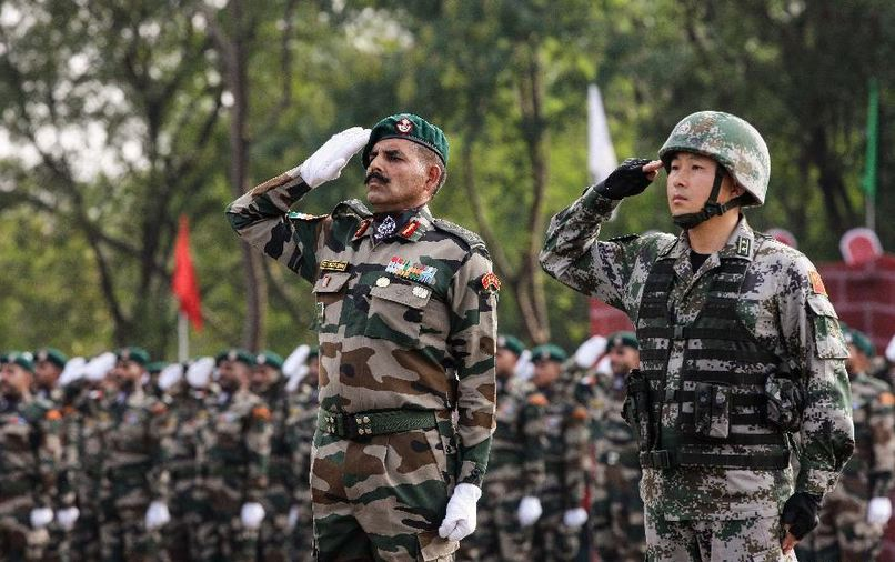 INDIA-PUNE-CHINA-MILITARY-JOINT TRAINING Indian and Chinese soldiers salute at the starting ceremony of the Hand-in-hand India-China Anti-Terrorism Joint Training Exercise in Pune, India, on Nov. 17, 2014. (Photo courtesy: Xinhua)