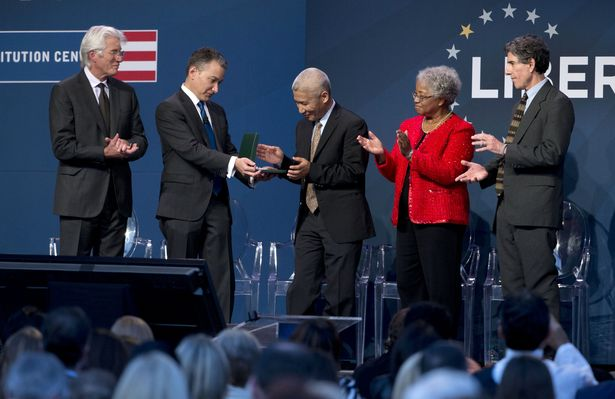 Thupten Jinpa, center, principal English translator to the Dalai Lama, accepts the Liberty Medal on his behalf from Jeffrey Rosen, second from left, President and Chief Executive Officer of the National Constitution Center during a ceremony at the National Constitution Center, Monday, Oct. 26, 2015, in Philadelphia. (Photo courtesy: DailyMail)