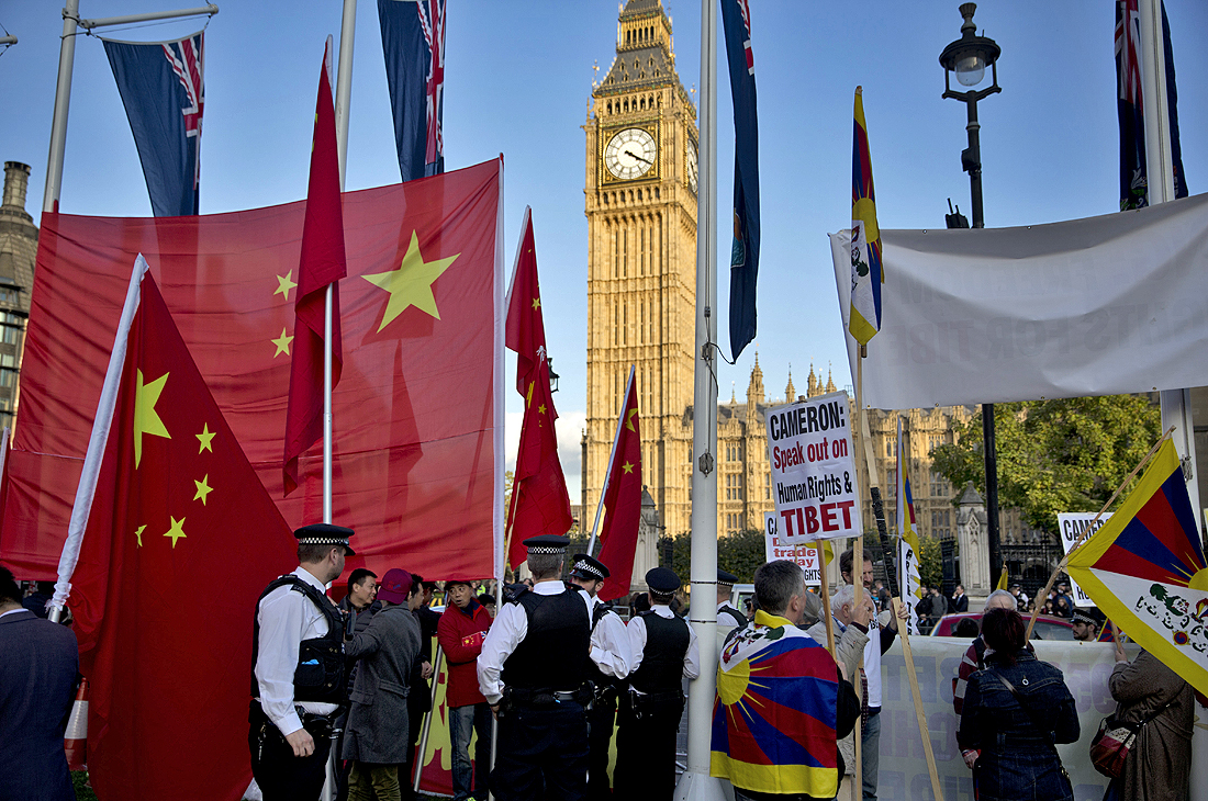 Supporters of Chinese President Xi Jinping, at left, stand separated by a line of police officers from human right campaigners, at right, holding a protest outside the Houses of Parliament where he was giving a speech in London, Tuesday, Oct. 20, 2015. Chinese President Xi Jinping arrived in Britain Monday for a four-day state visit as part of a push to increase trade ties between the two countries. (Photo courtesy: AP/Matt Dunham)