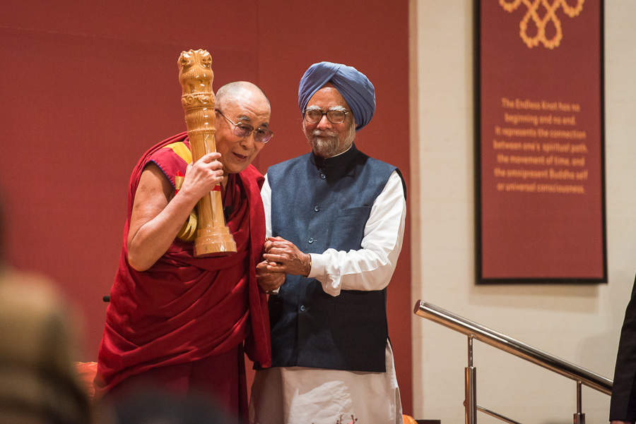 His Holiness the Dalai Lama Lama holding the National Emblem presented by Former Indian Prime Minister Dr Manmohan Singh at the 'Celebrating His Holiness' event in New Delhi, India on January 4, 2016. )(Photo courtesy/Tenzin Choejor/OHHDL)