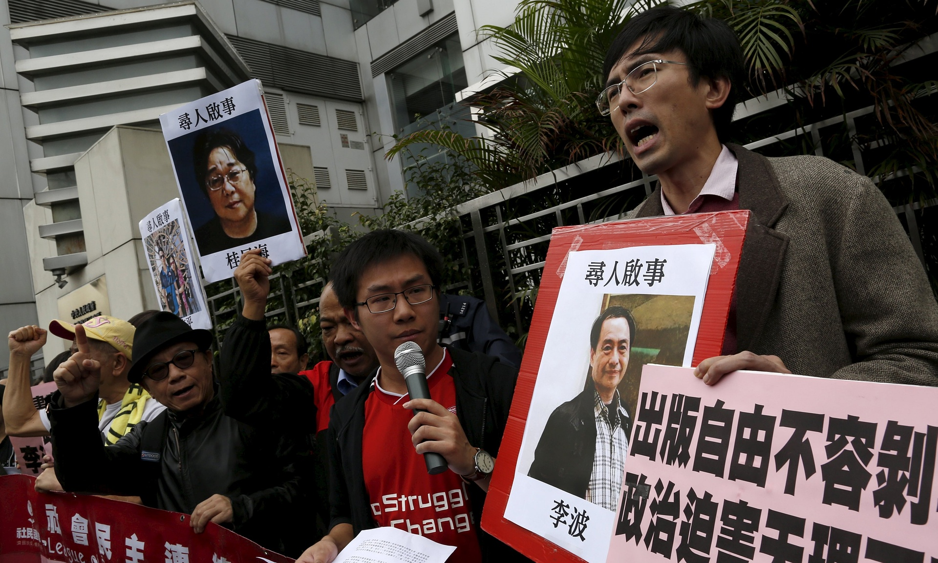 Demonstrators outside the Chinese liaison office in Hong Kong hold pictures of Lee Bo (right), Gui Minhai (left) and other Sage Communications employees who have gone missing. (Photo courtesy/Tyrone Siu/Reuters)