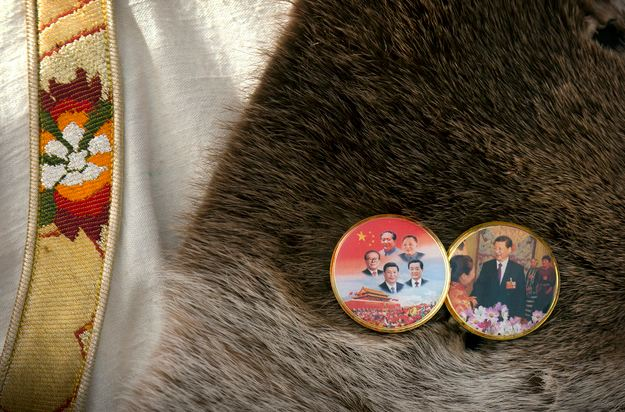 A National People's Congress (NPC) delegate from Tibet wears pins depicting five current and former Chinese leaders, left, and Chinese President Xi Jinping, right, as he leaves the Great Hall of the People following the opening session of the NPC in Beijing, Saturday, March 5, 2016. Along with their traditional robes, Tibetan delegates to the annual meeting of China's ceremonial parliament are sporting unique lapel pins displaying their loyalty to the Beijing leadership at a time of simmering tensions in their Himalayan homeland. (Photo courtesy/AP/Mark Schiefelbein)