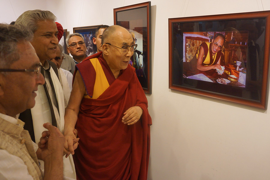 His Holiness the Dalai Lama looking at the 'Thank You Dalai Lama' Photo Exhibition at the All India Fine Arts & Crafts Society in New Delhi, India on April 10, 2016. (Photo courtesy/Jeremy Russell/OHHDL)