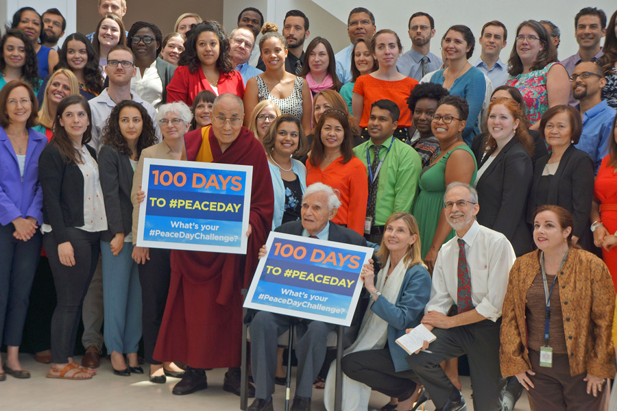 His Holiness the Dalai Lama with members of the United States Institute of Peace holding signs reminding of the upcoming International Peace Day after his conversation with USIP youth leaders in Washington DC, USA on June 13, 2016. (Photo courtesy/Jeremy Russell/OHHDL)