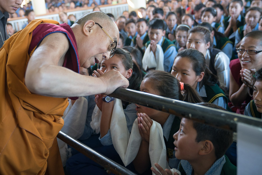 His Holiness the Dalai Lama greeting some of the more than 3000 Tibetan students gathered to attend his teachings on his arrival at the Main Tibetan Temple courtyard in Dharamsala, HP, India on June 1, 2016. (Photo courtesy/Tenzin Choejor/OHHDL)