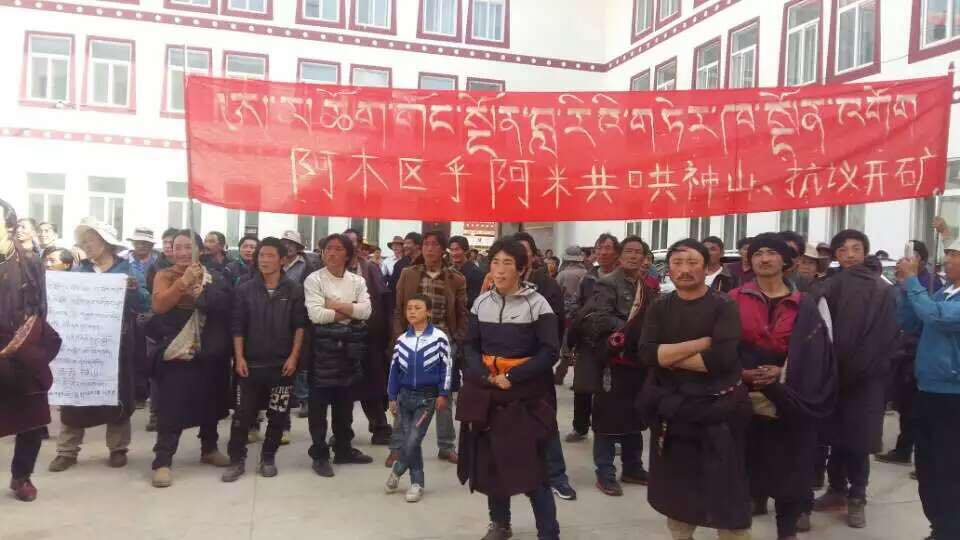 """Anti-mining protesters in Amchok with the banner the in background bearing the slogan: """"Stop Mining at Amchok Gong Ngon Lari!"""" (Photo courtesy: TCHRD)"""