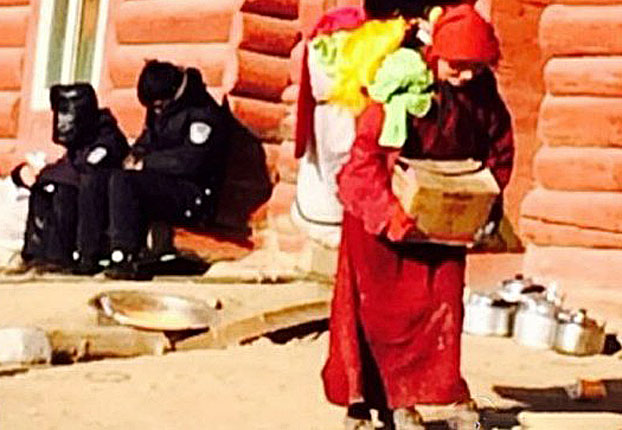 Watched by police, a Tibetan nun leaves her home at Larung Gar in an undated photo. (Photo courtesy: RFA)