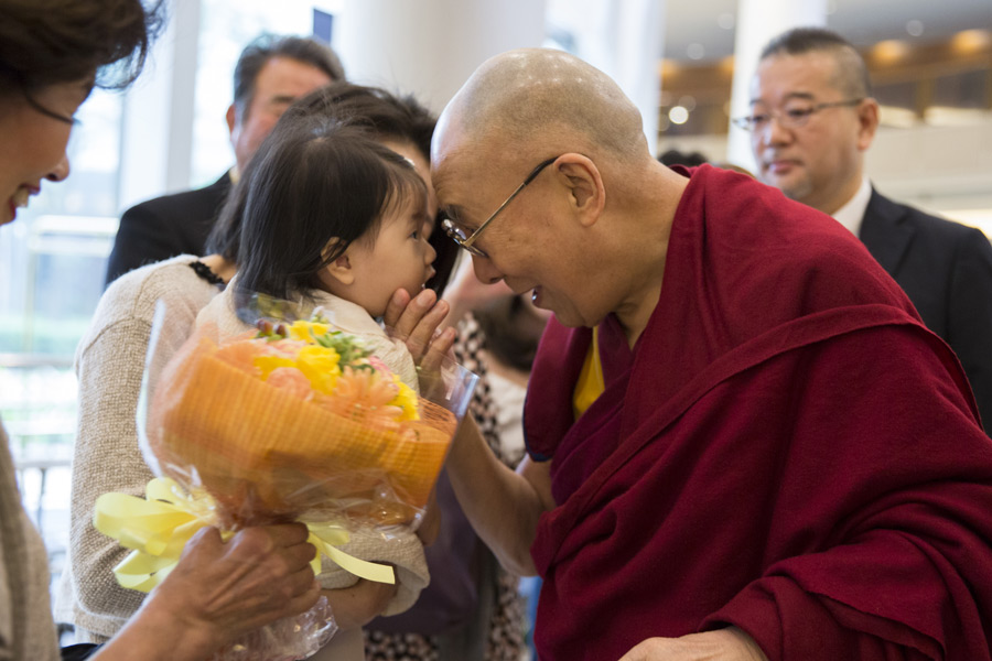His Holiness the Dalai Lama affectionately greeting a young child on his arrival at his hotel in Narita, Japan on November 8, 2016. Photo/Jigme Choephel