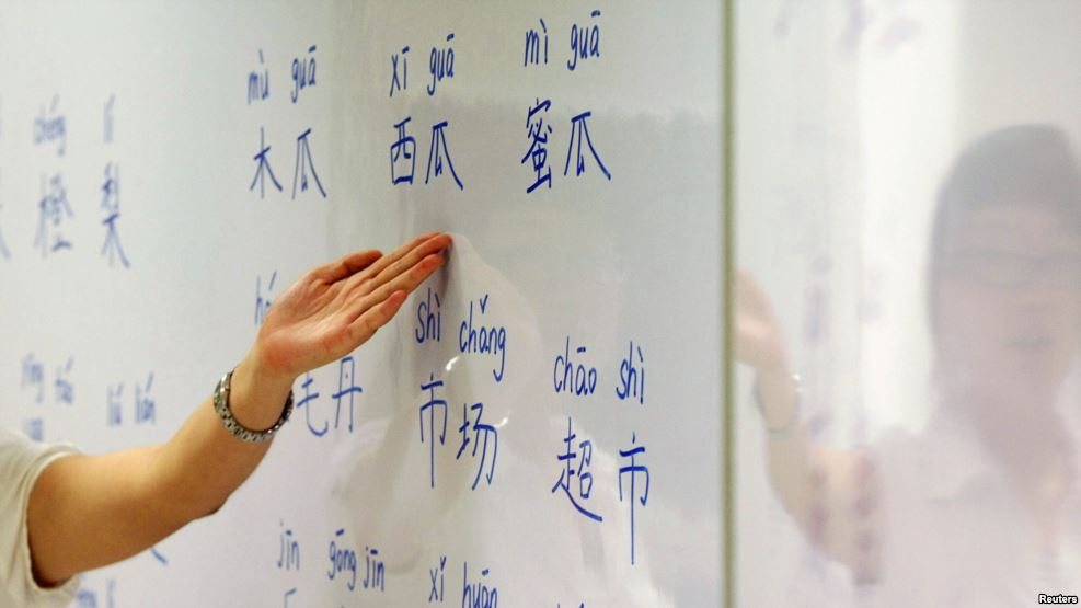An instructor points out Mandarin characters on a whiteboard at a night class for people learning Mandarin. (Photo courtesy: Reuters)
