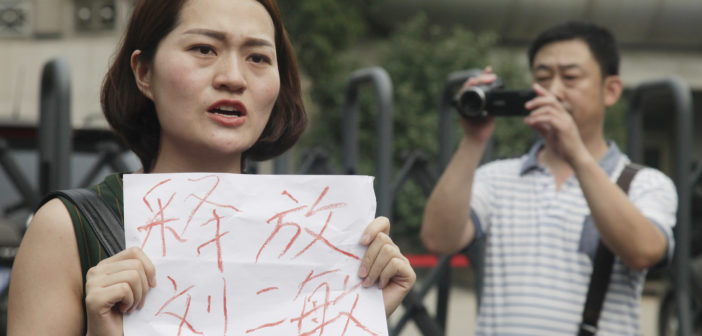 "Li Wenzu, left, wife of imprisoned lawyer Wang Quanzhang, holds a paper that reads ""Release Liu Ermin"" as she and supporters of a prominent Chinese human rights lawyer and activists stage a protest in Tianjin, China. File August 2016. (Photo courtesy: AP/Gerry Shih)"