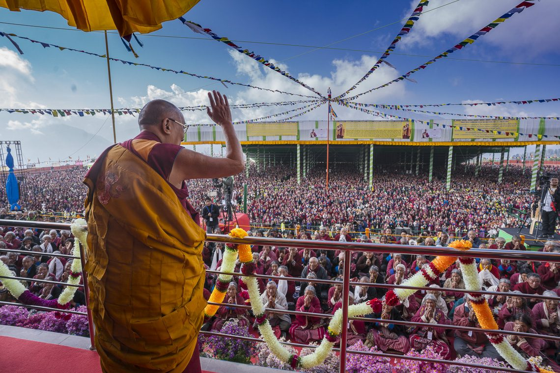 His Holiness the Dalai Lama waving to the crowd of over 50,000 on his arrival to Yiga Choezin teaching ground in Tawang. (Photo courtesy: Tenzin Choejor/OHHDL)