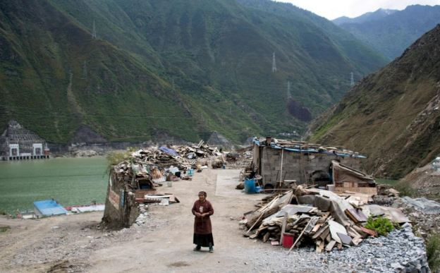 A woman stands next to the debris of demolished houses and her makeshift hut near Lianghekou in Sichuan province, the site of the latest huge dam to be built in China's drive for greener sources of power. (Photo courtesy: AFP)