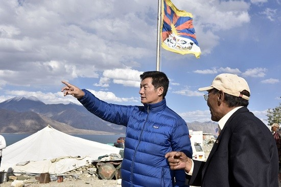 The Tibetan flag waves in the background as Lobsang Sangay, head of the Tibetan government-in-exile, gestures on the shore of Pang Gong lake. (Photo courtesy: tibet.net)