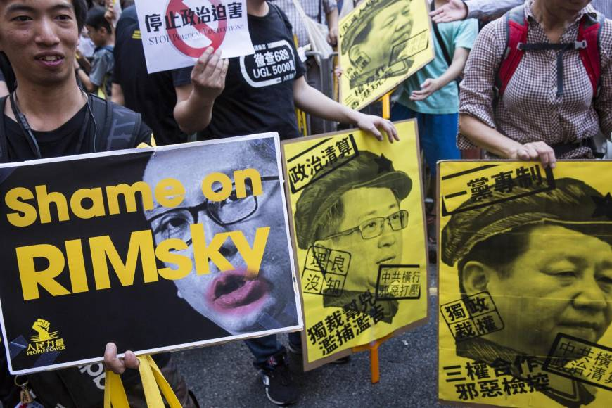Protesters hold placards during a march in Hong Kong on Sunday to protest the jailing of Joshua Wong, Nathan Law and Alex Chow (not pictured), the leaders of Hong Kong's 'Umbrella Movement,' after their sentencing at the High Court last week. (Photo courtesy: AFP-JIJI)