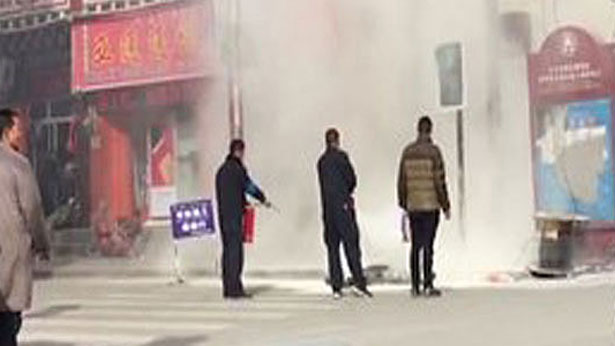 Screen grab from a video showing a police officer extinguishing the flames on Tibetan self-immolator Wangchuk Tseten, April 15, 2017. (Photo courtesy: RFA)