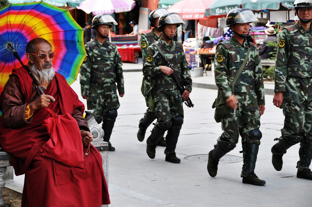 Chinese police pass a monk in Lhasa (Photo courtesy: Prasad Kholkute, Flickr)