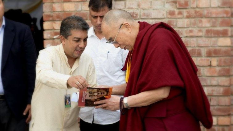 A copy of a translated version of 'My land and My People' being presented to His Holiness the Dalai Lama. (Photo courtesy: tibet.net)