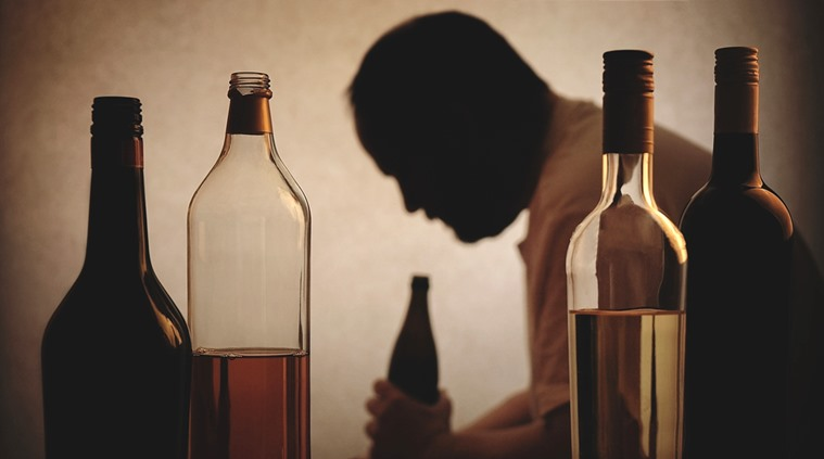 Representational art. Silhouette of a person drinking behind bottles of alcohol. (Photo courtesy; indianexpress)