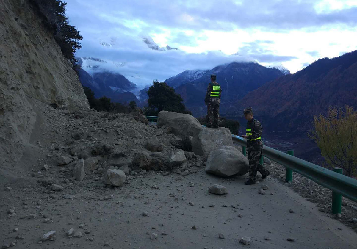 Rescuers look at a road blocked by fallen rocks in Paizhen town in Mainling county of Nyingchi city, Nov. 18, 2017.  (Photo courtesy: Liu Pengchao/Xinhua via AP)