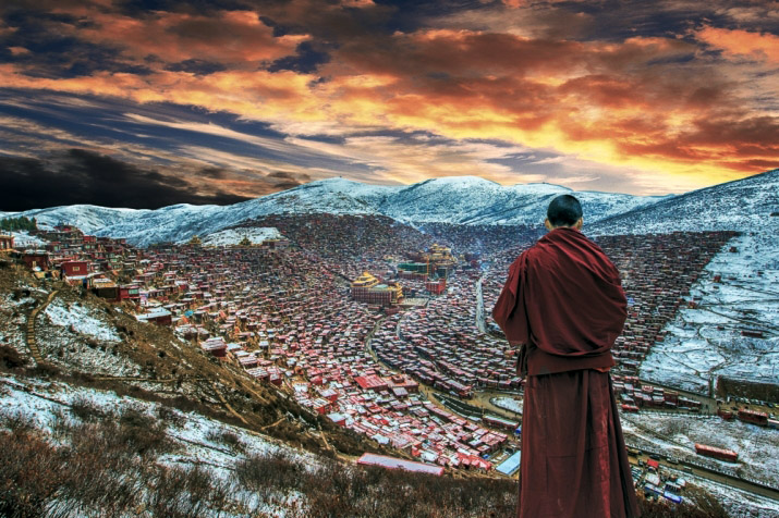 A monk stands on a hillside overlooking Larung Gar Buddhist Academy. (Photo courtesy: buddhistdoor.net)