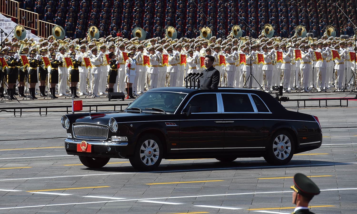 Chinese President Xi Jinping begins a review of troops from a car during a military parade at Tiananmen Square in Beijing on September 3, 2015, to mark the 70th anniversary of victory over Japan and the end of World War II. China kicked off a huge military ceremony marking the 70th anniversary of Japan's defeat in World War II on September 3, as major Western leaders stayed away. (Phtoo courtesy: AFP/ GREG BAKER)