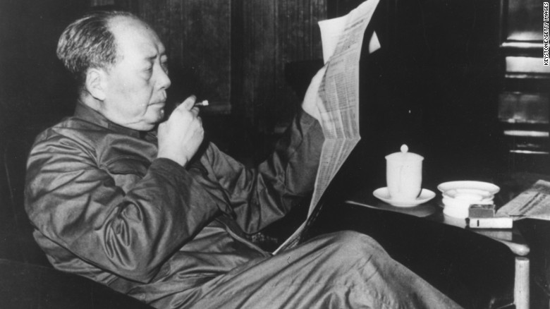 Mao Zedong (1893-1976), Chinese Communist leader, reading a newspaper and smoking a cigar. (Photo courtesy: CNN)